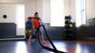 Woman Training in Gym with Battle Ropes