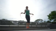 Woman training outdoors jumping rope