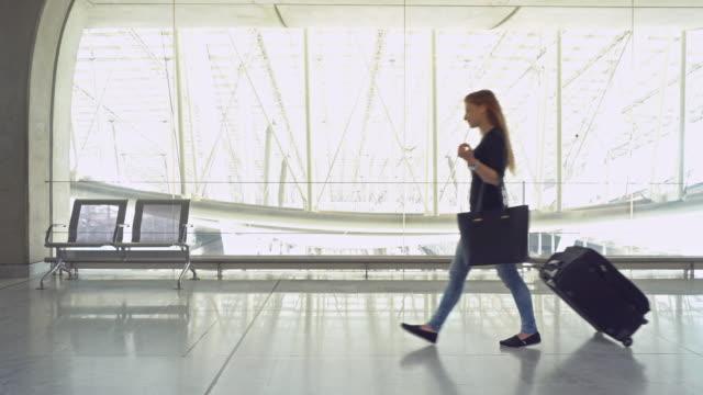 Woman traveler with luggage walking through airport terminal