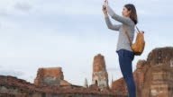 Woman traveller using mobile phone for take a photos at ayutthaya historical park Thailand