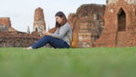 Woman Traveller using smartphone for searching information in ayuthaya historical park