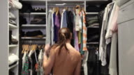 T/L MS Woman trying on bunch of different outfits in walk-in closet, New York City, New York, USA