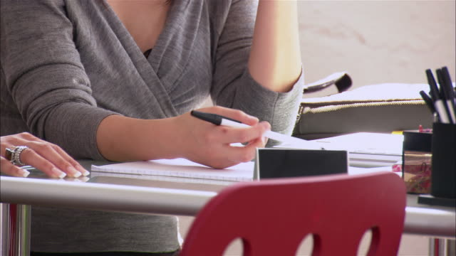 Woman twirling pen at desk / zoom out to woman in discussion with coworker / New York City
