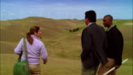 MS Woman + two businessmen surveying landscape near wind turbines on hill / Livermore, California, USA