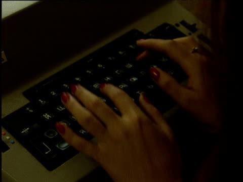 Woman types on antiquated electronic Russian typewriter Uzbekistan