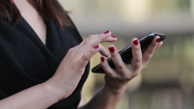 'CU A woman types on her smartphone / Brasilia, Brazil'