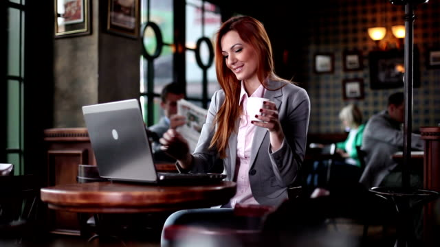 Woman typing at laptop and drinking coffee.