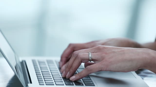 woman typing on laptop keyboard