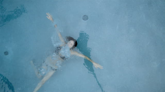 SLO MO OVERHEAD MS woman underwater in swimming pool/Connecticut, USA