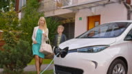 DS Woman unplugging the car while talking to son