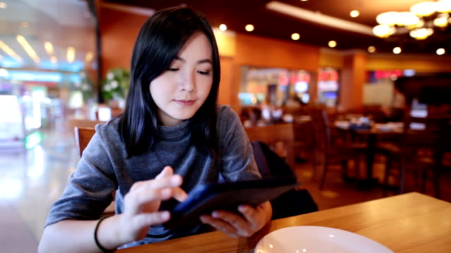 Woman use digital tablet in restaurant