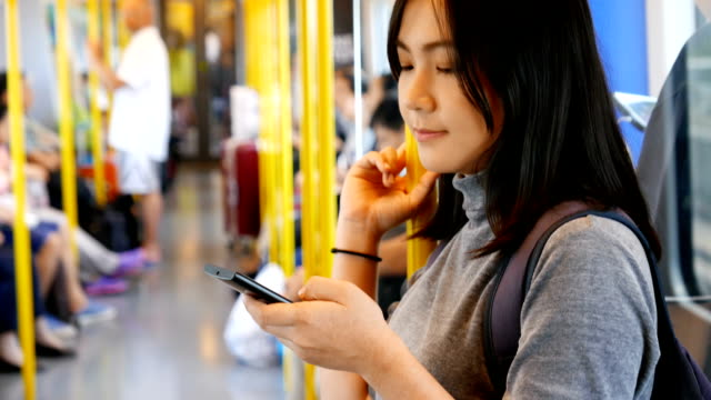 Woman use social media for communication in the sky train