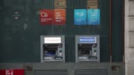 A woman uses a cash machine beneath a Yorkshire Bank sign in Piccadilly Circus London United Kingdom on Friday November 14 a Clydesdale Bank window...