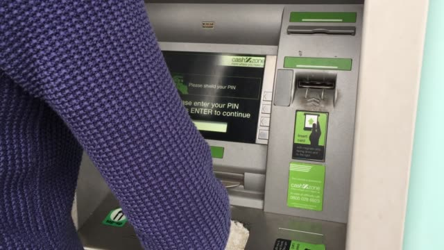 A woman uses a cashpoint ATM on November 3 2017 in Bristol England The Bank of England raised interest rates from a historic low for the first time...