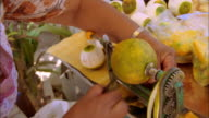 Woman uses a mechanical tool to core and peel fruit, Belize Available in HD.