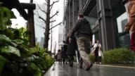 A woman uses a smartphone as a customer exits a bank in Tokyo Japan on Friday March 31 Men in business suits hold umbrellas as they cross a road in...