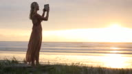 Woman uses digital tablet above beach at sunrise, surf behind