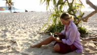 Woman uses digital tablet on beach, below leafy tree