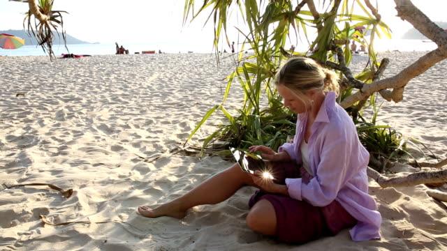 Woman uses digital tablet on beach, below leafy tree