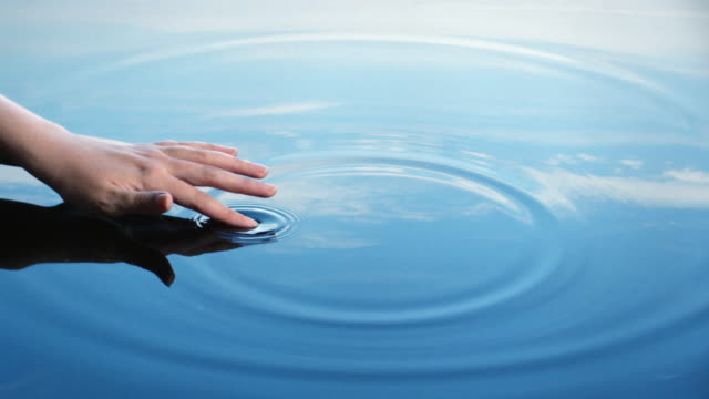 A woman uses her finger to create riples in water reflected in a blue sky.