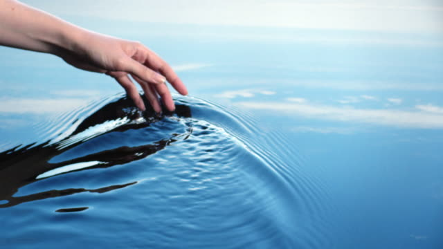 A woman uses her hand to create riples in water reflected in a blue sky.