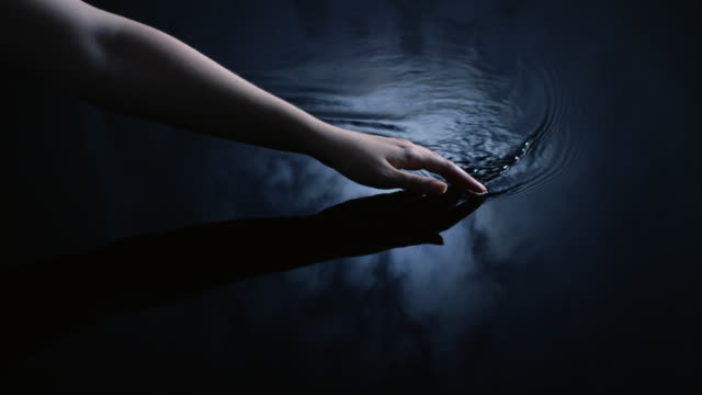 A woman uses her hand to create ripples in water reflected in a moonlit sky.