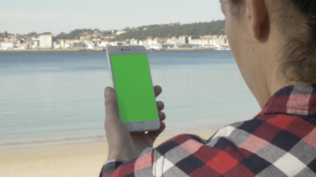 Woman uses his smartphone with green screen