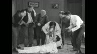 Woman uses pepper to rouse sleeping Buster Keaton, everyone in the room starts sneezing and men push a surprised Keaton around