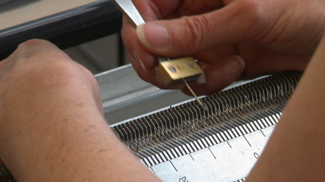 Woman Uses Tool to Adjust Loops on a Knitting Machine