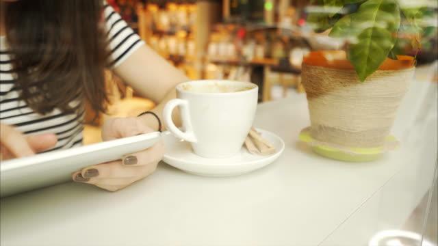 Woman using a digital tablet in coffee shop.