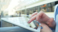 Woman using a digital tablet on the railroad station platform.