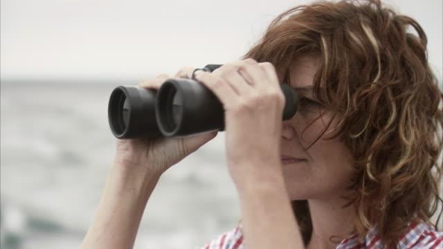A woman using a pair of binoculars Stockholm archipelago Sweden.