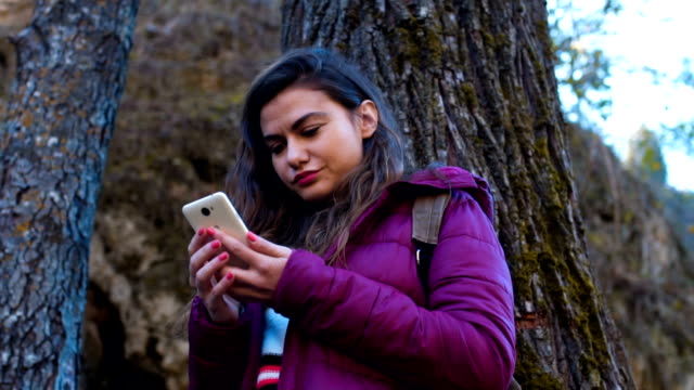 Woman using a phone near waterfall
