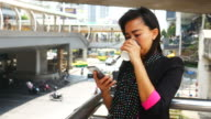 woman using a smart phone and drink coffee in urban backgrounds