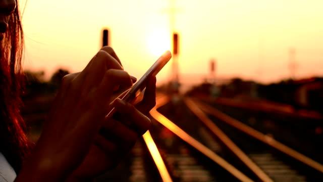 Donna utilizzando smartphone sulla ferrovia.