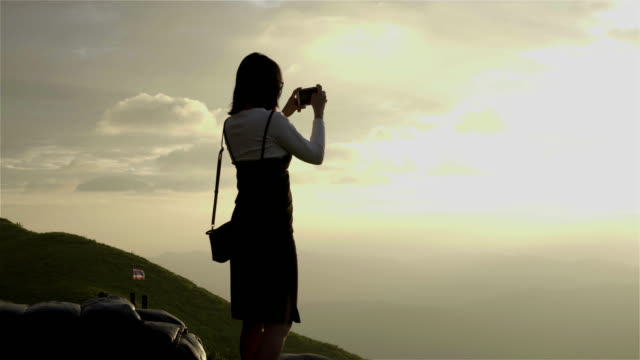 4K: woman using a smartphone to take a sunset.