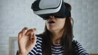 Woman using a virtual reality glasses at home