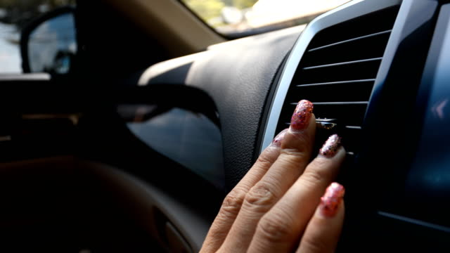 woman using air conditioner in car