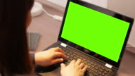 Woman using and typing on laptop keyboard with a green screen
