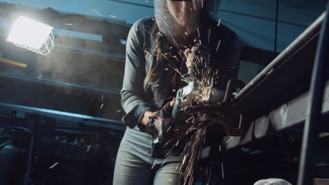 Woman Using Angle Grinder from Below