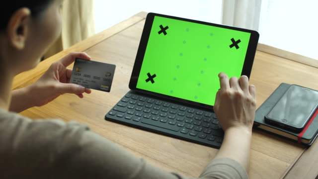 Woman Using Credit card with Digital Tablet green screen, Chroma key