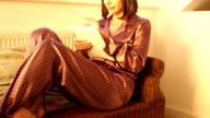 Donna con Tavoletta digitale vicino alla finestra in pigiama