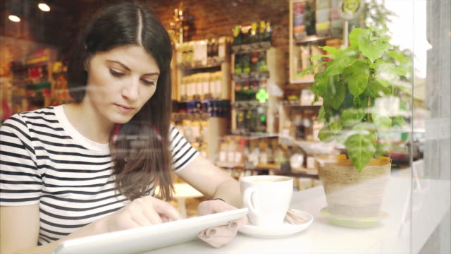 Woman using digital tablet in a coffee shop.