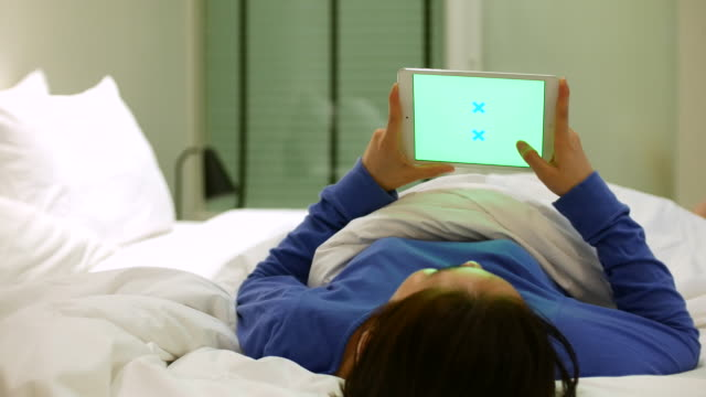 Woman using digital tablet in bed with Green screen, 4k(UHD)