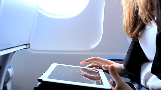 Frau mit digitalen tablet auf Flugzeug