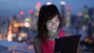CU Woman using digital tablet with in front of city lights