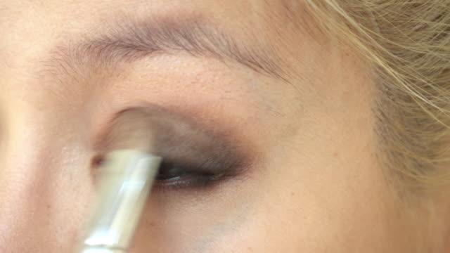 woman using eyeshadow blush makeup beauty
