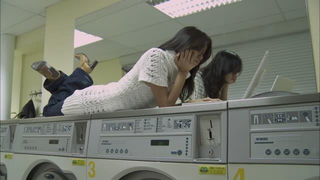 WS Woman using laptop in laundromat / Brussels, Belgium