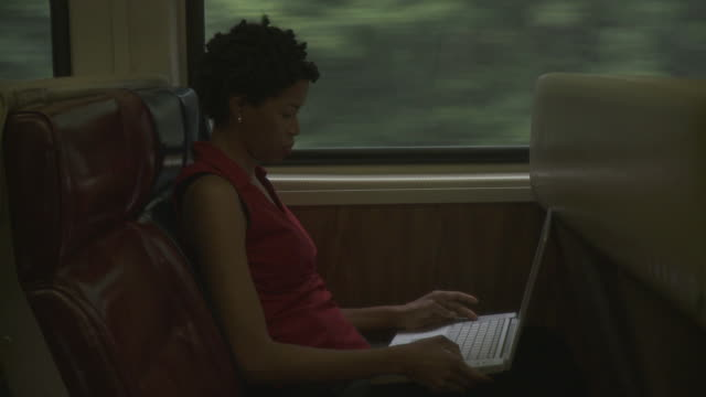 MS Woman using laptop in moving commuter train / New York City, New York, USA