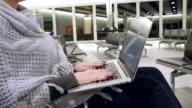 Donna utilizzando un computer portatile in sala d'attesa